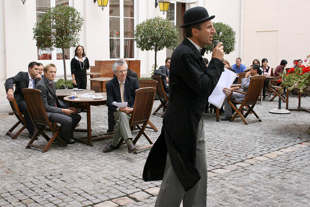 Hercule Poirot announces the crime to teams of young detectives in the courtyard of a Parisian hotel
