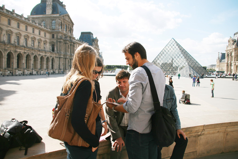 A team tries to find a code in the Louvre courtyard with the pyramid behind them
