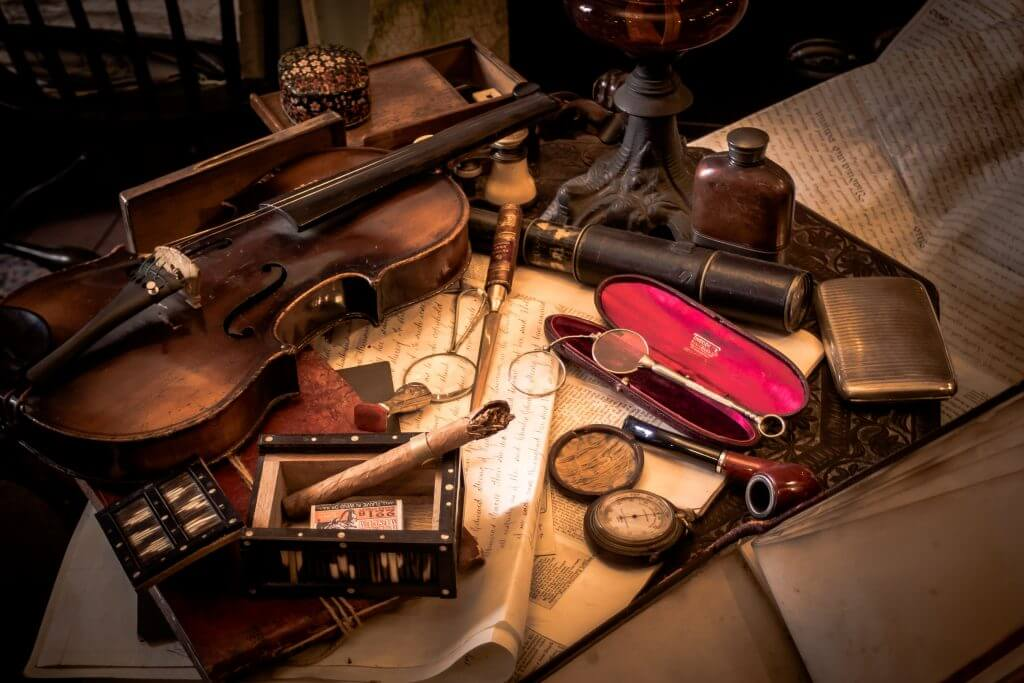 photo of antique objects: violon, cigar, maps, indicating knowledge on a variety of subjects