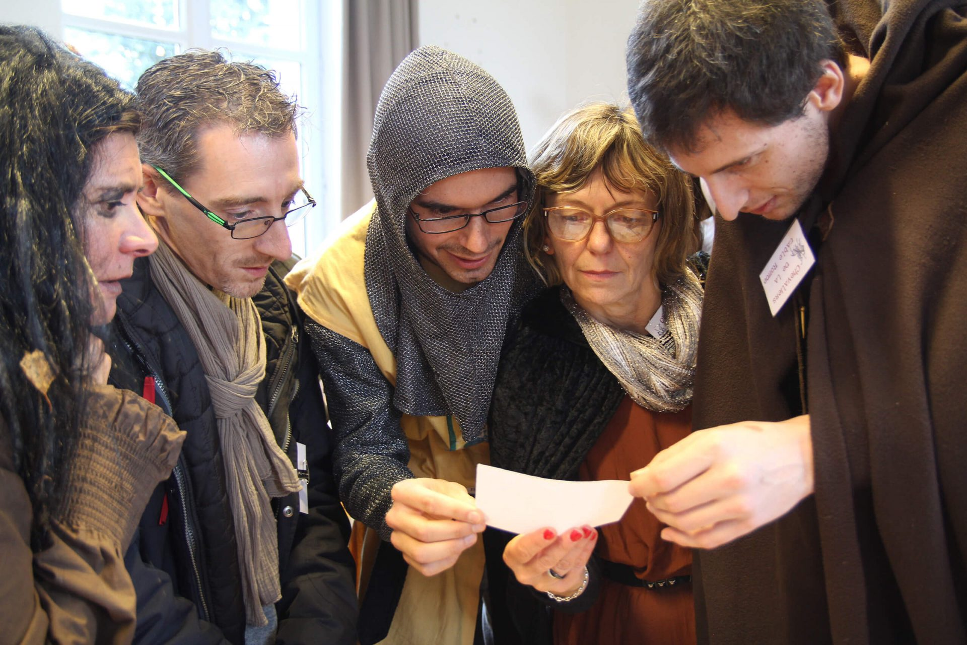 team building challenge - a group in medieval costume crowd together to analyse a clue