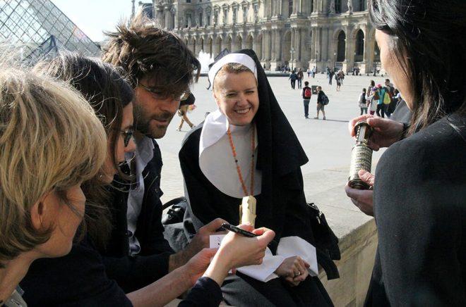 Avec le Louvre et le pyramide en arrière fond, la bonne-soeur-animatrice est en plein échange avec une équipe.