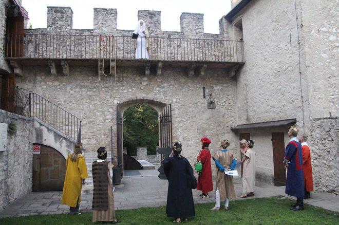 Merlin présente l'énigme aux participants portant des costumes médiévales